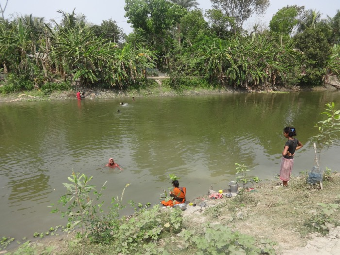 Ladies taking bath in pond